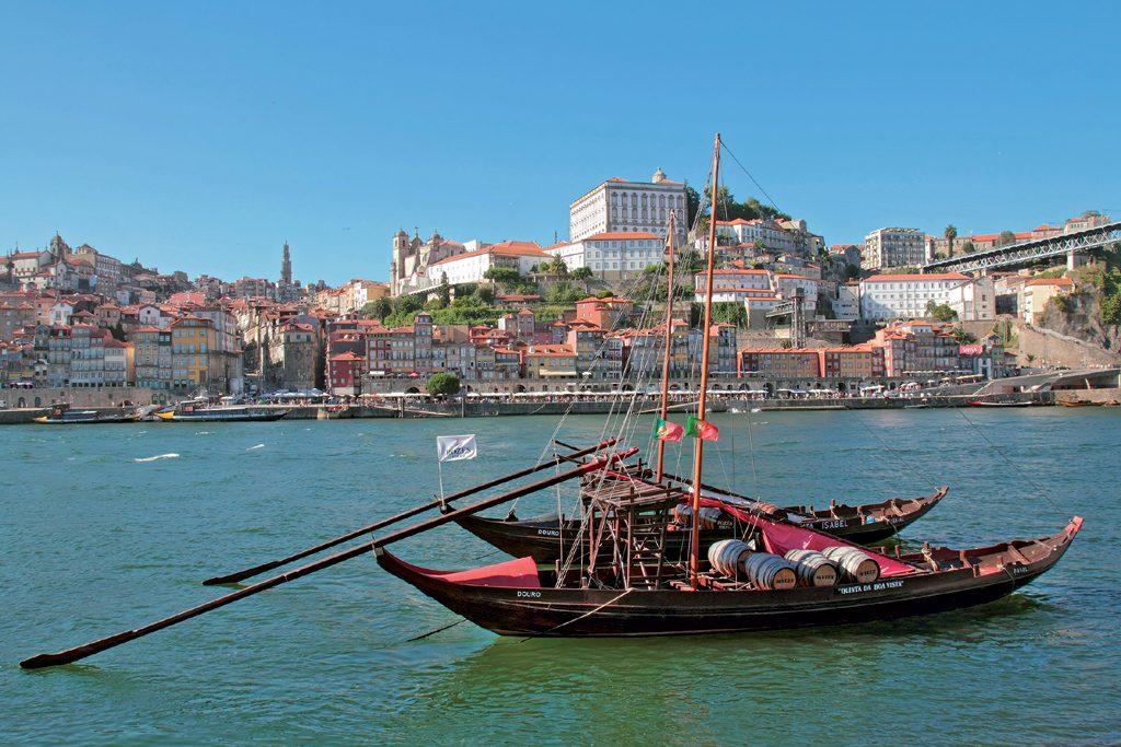 Stadt Porto und im Vordergrund der Fluß Douro mit zwei Boten.