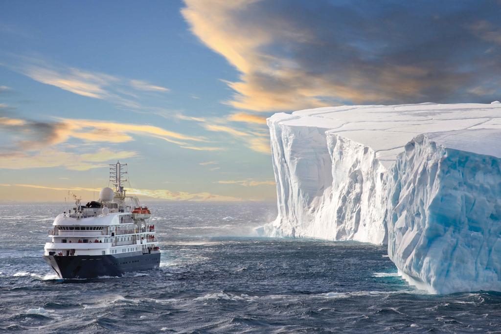 Kreuzfahrtschiff an einem riesigen Eisberg.