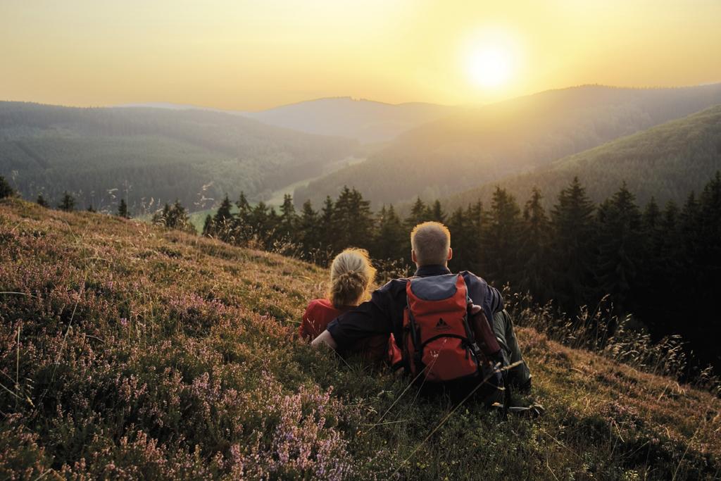 Wanderpaar sitzt auf Hügel und schaut sich Sonnenuntergang an.